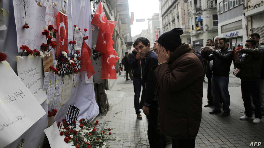 A man reacts in front of a makeshift memorial at the location of the blast of a suicide attack on Istiklal Street, a major shopping and tourist district, in central Istanbul, March 20, 2016.