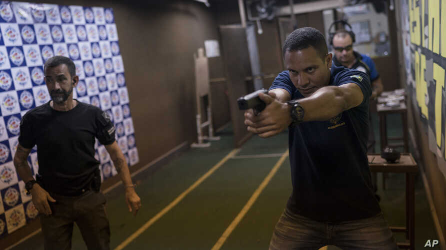 Shooting instructor Alex Cordeiro, right, holds a fake pistol as he demonstrates a movement to Rildo Anjos, owner of the Calibre 12 gun club, during a practice session in Sao Goncalo, Brazil, Jan. 10, 2019.