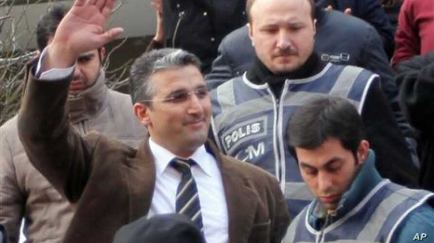 Nedim Sener, a leading investigative reporter of daily newspaper Milliyet, waves after police detained him in Istanbul, Turkey, Thursday, March 3, 2011. Police detained about 10 people, mostly journalists, including Sener, in a crackdown on an allege