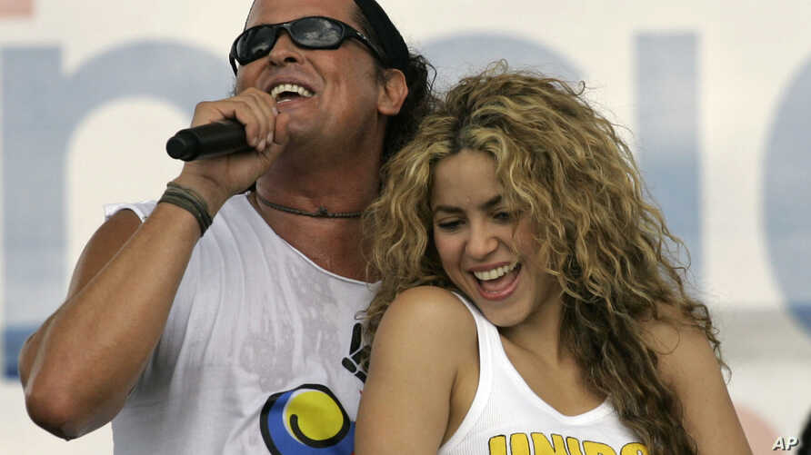 """FILE -  Colombian singers Shakira, right, and Carlos Vives perform during a """"concert for peace"""" Independence Day celebrations in Leticia, Colombia."""