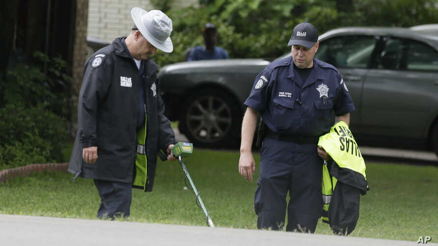 Dallas County Sheriff crime scene investigators use a metal detector at the intersection near where a black teenager was killed by a white police officer, May 3, 2017.