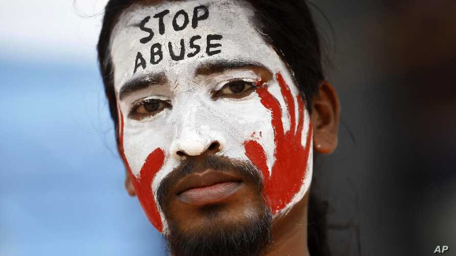 An Indian protester with a slogan painted on his face participates in a demonstration to protest against police inaction after a 6-year-old was allegedly raped in a school in Bangalore, India, July 20, 2014.