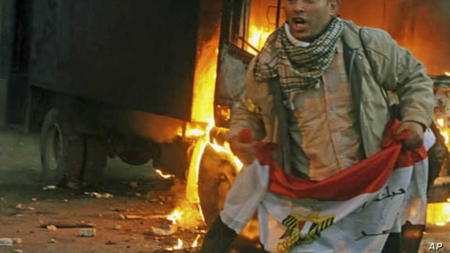 A protester holds an Egyptian flag next to a police vehicle that was set ablaze during clashes between protesters and security forces in Cairo, November 19, 2011.