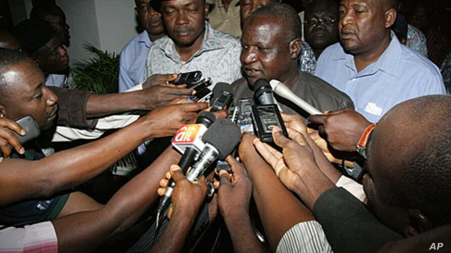 Journalists swarm Nigeria Labor Congress chief Abdulwahed Omar (C) on January 15, 2012 at the state house in Abuja, Nigeria.