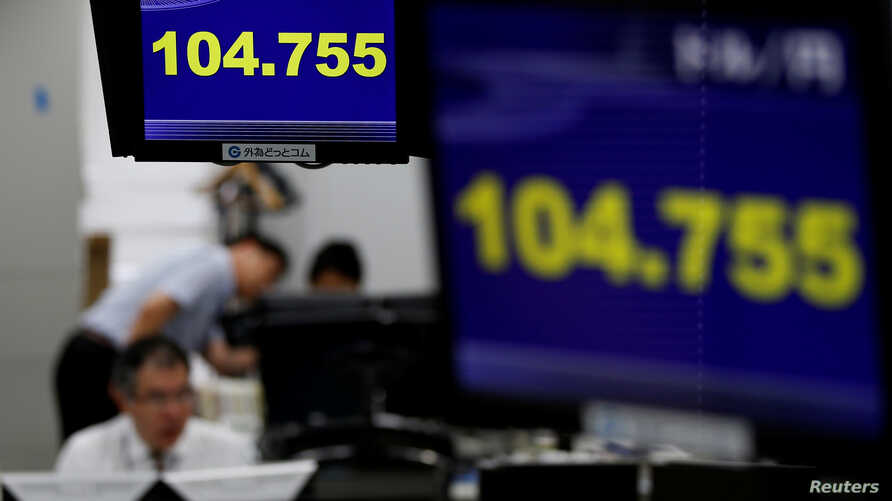 Employees of a foreign exchange trading company work under monitors displaying the Japanese yen's exchange rate against the U.S. dollar in Tokyo, Japan, June 16, 2016.