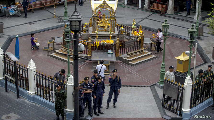 FILE - Thai police stand guard as people pray during a crime re-enactment near the bomb site at Erawan shrine in central Bangkok, Thailand, Sept. 9, 2015.