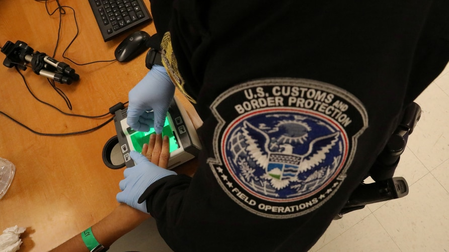 A woman who is seeking asylum has her fingerprints taken by a U.S. Customs and Border patrol officer at a pedestrian port of entry from Mexico to the United States, in McAllen, Texas, May 10, 2017.