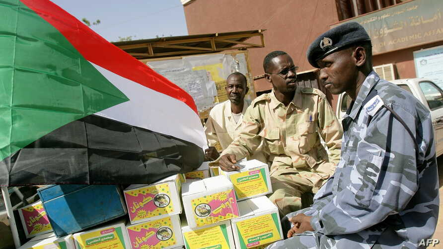 A Sudanese national flag is fixed by students heading to fight on the border with South Sudan on truck packed with relief aid at the University of Science and Technology in Khartoum, April 17, 2012.