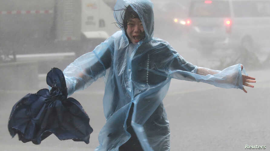 A woman runs in the rainstorm as Typhoon Mangkhut approaches, in Shenzhen, China, Sept. 16, 2018.