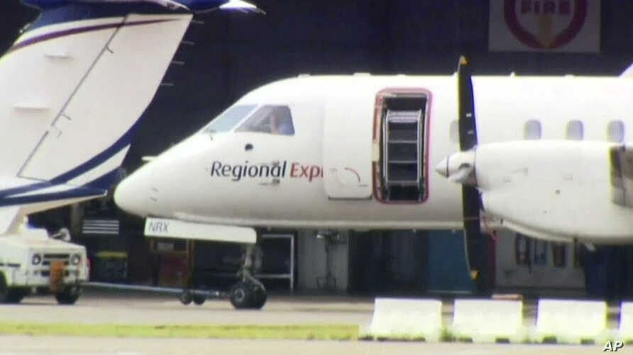 This image made from video shows a passenger plane being moved at Sydney Airport, in Sydney, Australia, March 17, 2017. The plane landed safely Friday after one of its two propellers fell off in an extraordinary emergency as it approached the airport