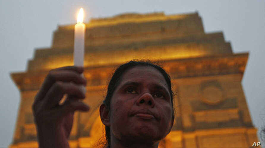 A mourner attends a candlelight prayer ceremony for nun Valsha John at the India Gate in New Delhi, November 22, 2011. John, 52, was beaten and hacked with an axe by unknown assailants in India's eastern Jharkhand state where she had led a campaign f