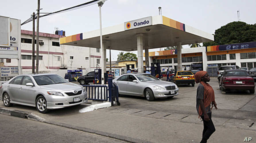 A woman walks past cars buying fuel at a gas station in Lagos, Nigeria, April 24, 2012.