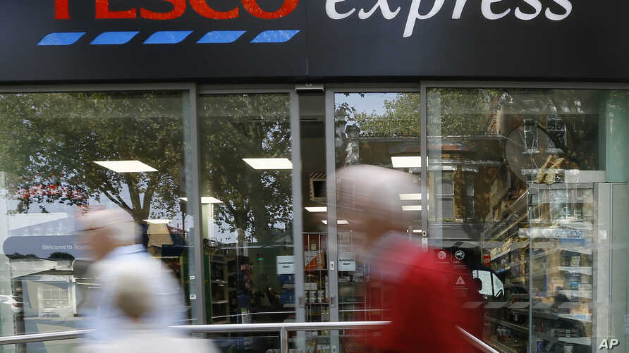FILE - Tesco, Britain's largest retailer by revenue, plunged to an annual loss of 6.4 billion pounds ($9.5 billion) Wednesday. Pedestrians pass a Tesco shop in London, Sept. 22, 2014.