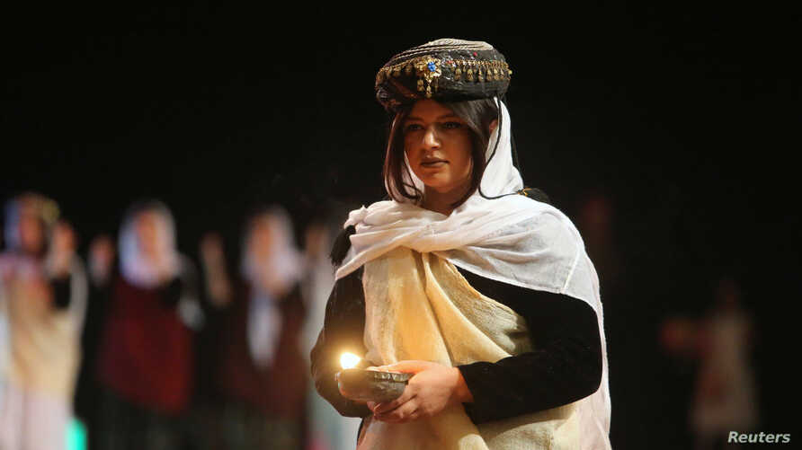 Yazidis traditional group performs during the commemoration of the third anniversary of what the United Nations said was a genocide, in Duhok, Iraq, Aug. 3,2017.