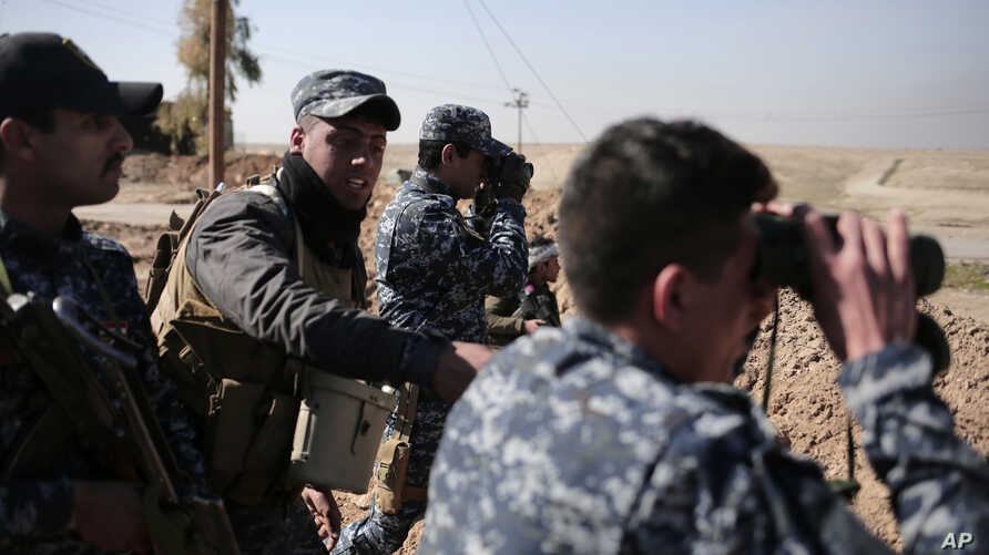Federal police officers look towards Islamic State group territory as civilians flee the area, in the town of Albu Saif, Iraq, Feb. 21, 2017. A military spokesman says Iraqi forces are consolidating their gains south of Mosul ahead of moving deeper i