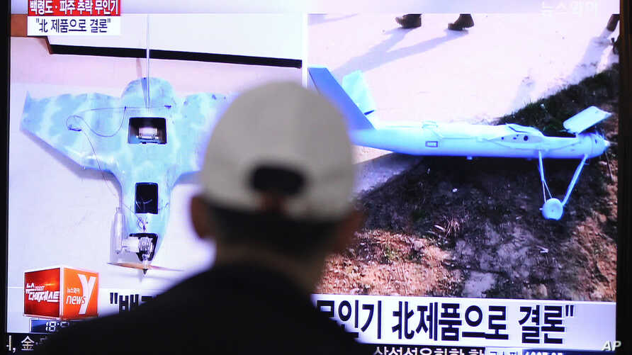 FILE - A man watches a TV news program showing unmanned drones, at the Seoul Railway Station in Seoul, South Korea, Wednesday, April 2, 2014