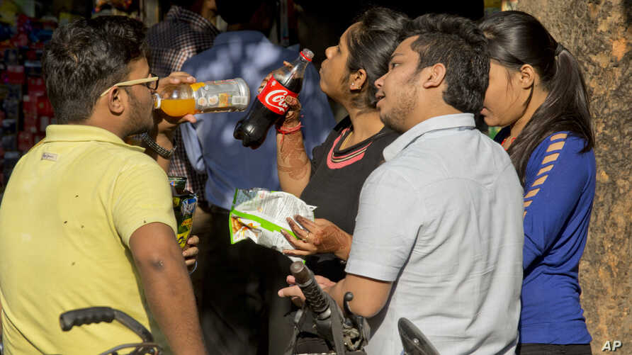 Indian teenagers eat and drink outside a street food stall, in New Delhi, March 9, 2016.