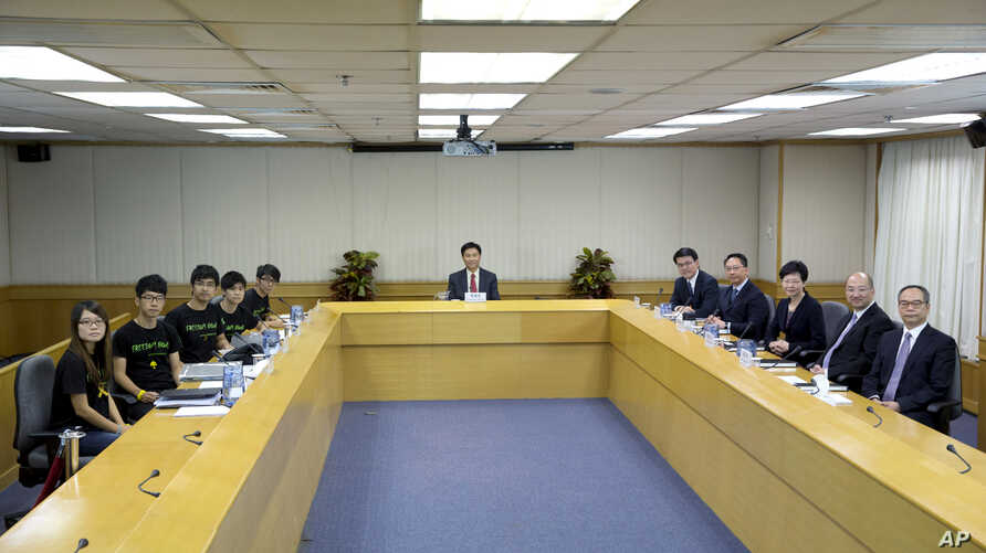 Hong Kong government officials line the right side of the table, Lingnan University president Leonard Cheng, center, and student leaders line the left side of the table as talks between Hong Kong officials and students begin, Oct. 21, 2014.