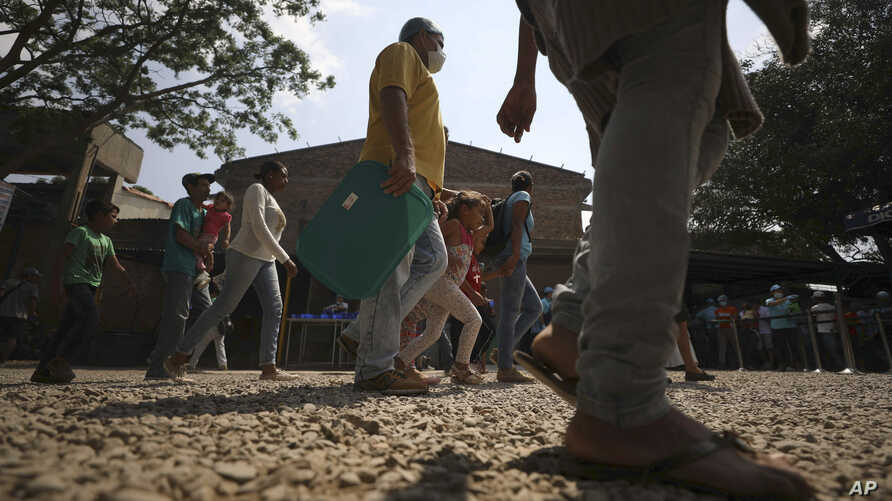 """Venezuelan migrants arrive at the """"Divina Providencia"""" migrant shelter to receive a free lunch in La Parada, near Cucuta, on the border with Venezuela, Colombia, Monday, Feb. 11, 2019."""