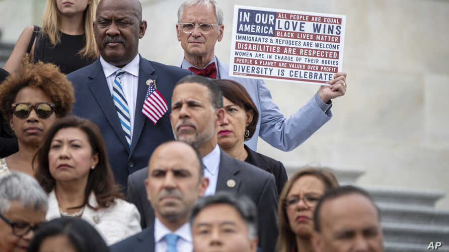 Rep. Earl Blumenauer, D-Ore., holds a sign as House Democrats gather on the steps of the Capitol to call for passage of the Keep Families Together Act, legislation to end the Trump Administration's policy of separating families at the US-Mexico borde