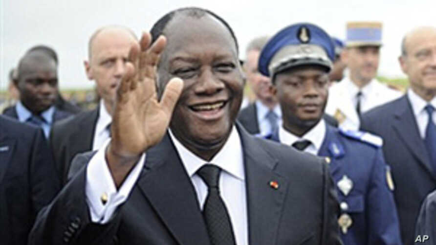Ivory Coast President Alassane Ouattara waves next to French president Nicolas Sarkozy (not seen) on May 21, 2011 at the airport in Yamoussoukro