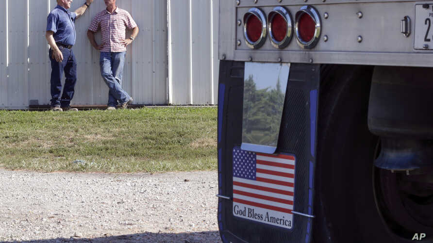 FILE - Farmer Don Bloss, left, talks to his son Mark behind a grain truck on his farm in Pawnee City, Nebraska, July 12, 2018.