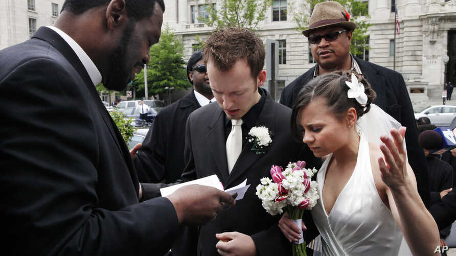 Bishop Harry R. Jackson Jr., of Beltsville, Md., left, prays with Jonathan Paul Ganucheau, 24, and Denise Buckbinder Ganucheau, 26, both of Dallas, Texas, before performing a religious wedding ceremony in Washington, May 5, 2009.