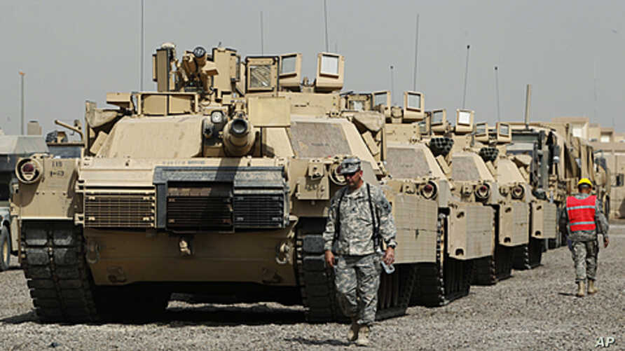 U.S. soldiers walk past tanks at a courtyard at Camp Liberty in Baghdad. U.S troops are scheduled to pull out of the country by the end of this year, according to a 2008 security pact between the U.S. and Iraq, (File September 30, 2011).