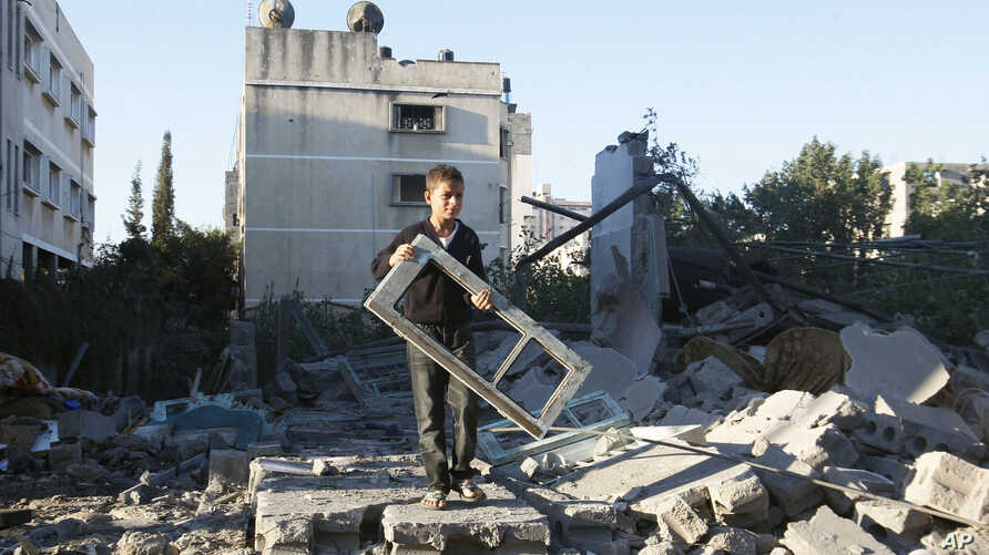 A Palestinian boy holds a window pane taken from a damaged house hit in an Israeli strike, in Gaza City, November 15, 2012.s