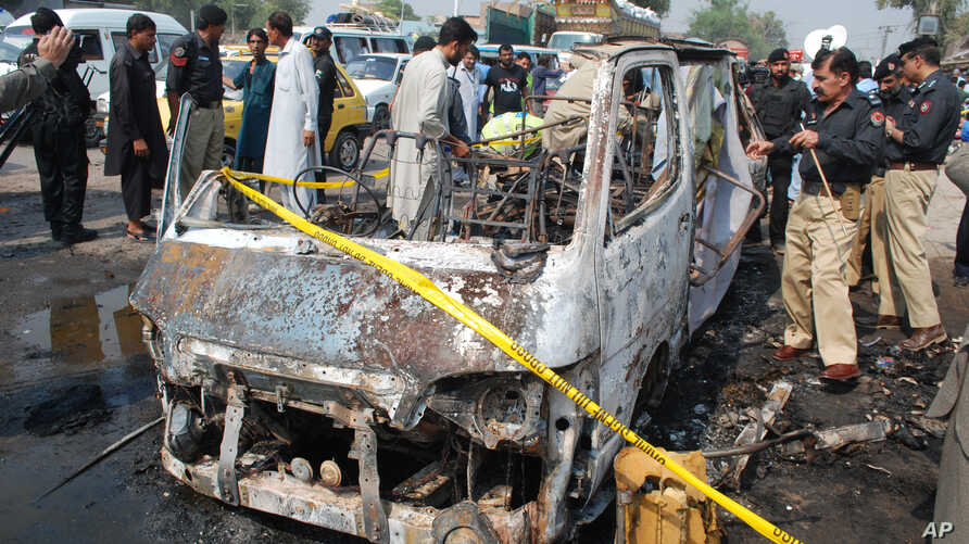 Pakistani police officers look at a damaged vehicle following blast in Peshawar, Pakistan, Oct. 2, 2014.