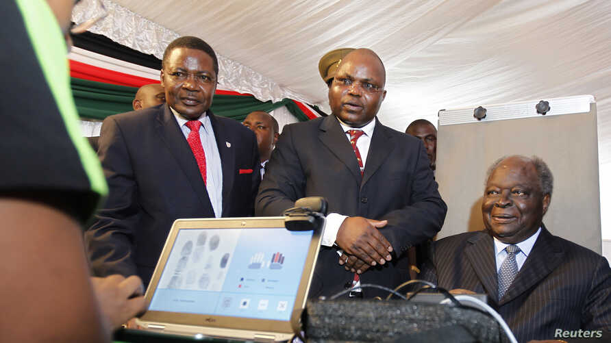 Kenyan President Mwai Kibaki (R) registers as a voter before launching the nationwide, one-month biometric voter registration (BVR) exercise in the capital Nairobi, November 19, 2012, targeting over 18 million voters ahead of the March 4 General Elec
