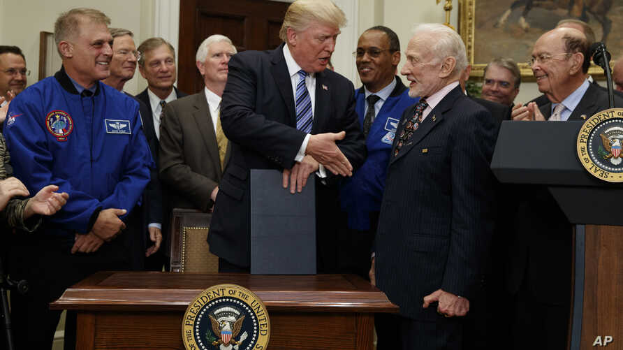 President Donald Trump shakes hands with former astronaut Buzz Aldrin after signing an executive order to establish a National Space Council, June 30, 2017, in the Roosevelt Room of the White House in Washington.