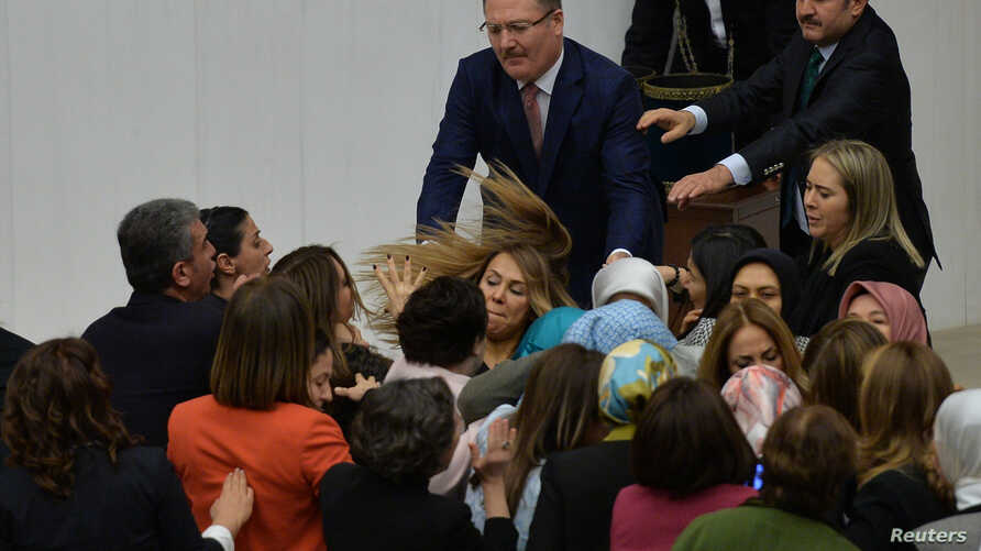 Ruling AK Party and opposition lawmakers scuffle after the independent lawmaker Aylin Nazliaka (not pictured) handcuffed herself to the rostrum during a debate to protest against the proposed constitutional changes at the Turkish Parliament in Ankara...