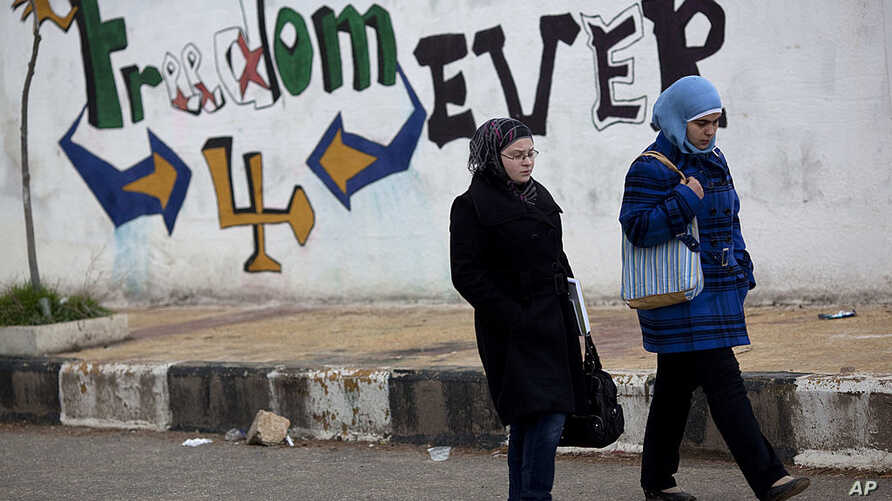 """Women walk pass graffiti that reads """"Freedom for Ever"""" on the outskirts of Idlib, north Syria. (AP)"""