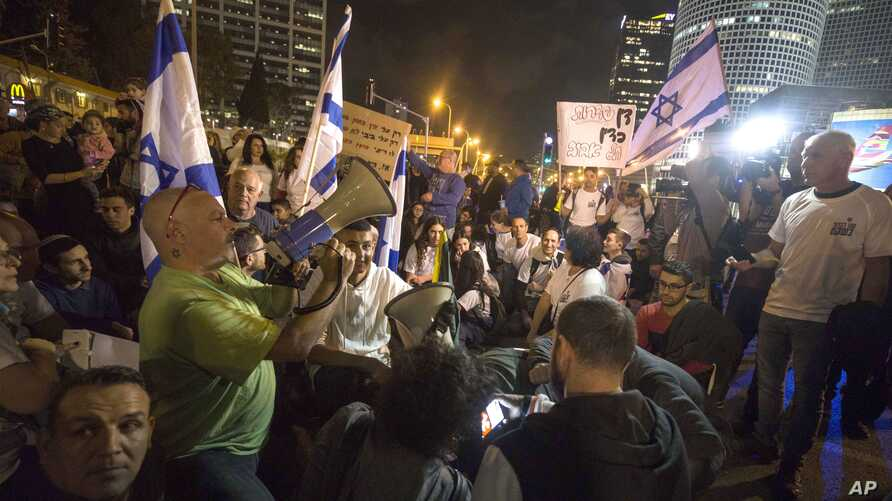 Israeli protesters hold flags and chant slogans during a demonstration against the cease-fire between Israel and Gaza's Hamas in Tel Aviv, Israel, Thursday, Nov. 15, 2018.