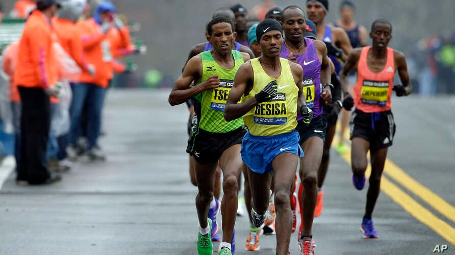Lelisa Desisa, of Ethiopia, leads the pack past a water staion, in Natick, Mass., en route to a win in the Boston Marathon, April 20, 2015.