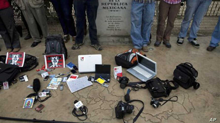 "Members of the press stand by their working tools as they protest violence against journalists at the border by a sign that reads in Spanish ""Limit of the Mexican Republic"" in Tijuana, Mexico, 7 Aug 2010"