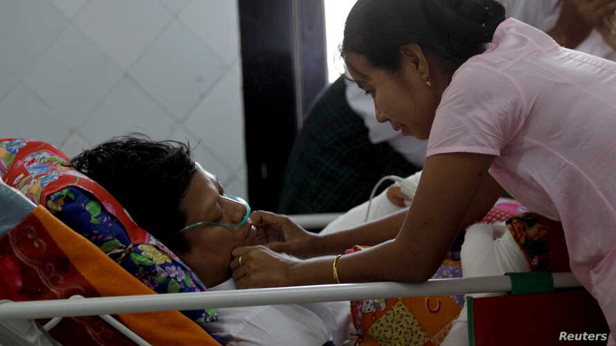 Naing Ngan Lynn, a candidate for National League for Democracy (NLD) party who was attacked on Thursday evening, lies on a hospital bed as his wife takes care of him in Yangon General hospital in Yangon, Myanmar, October 30, 2015.
