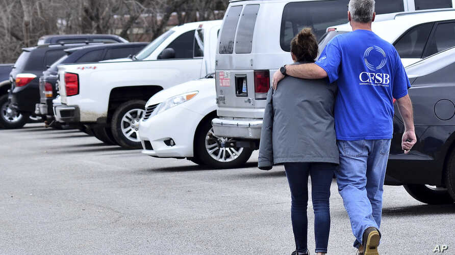 Family members escort their children out of Marshal North Middle School near Palma, Ky., Jan. 23, 2018, after the students were taken there from Marshal High School.