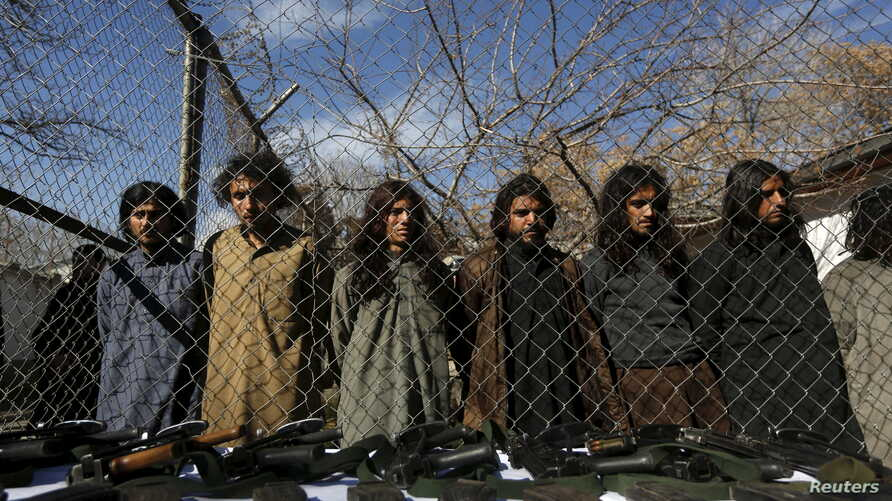 Pakistani Taliban fighters, who were arrested by Afghan border police, stand during a presentation of seized weapons and equipment to the media in Kabul, Afghanistan, Jan. 5, 2016.