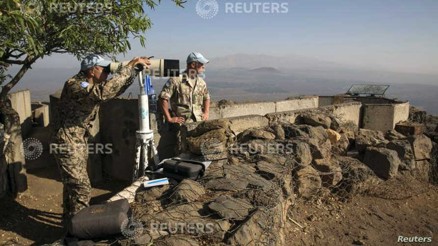 A member of the United Nations Disengagement Observer Force (UNDOF) looks through binoculars at Mount Bental, an observation post in the Golan Heights that overlooks the Syrian side of the Qunietra crossing Aug. 31, 2014.