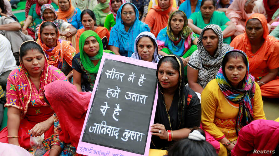 Family members of sanitation workers attend a protest against the rising deaths of people cleaning sewers, in New Delhi, India, Sept. 25, 2018.