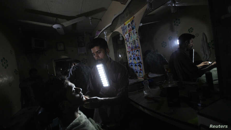A barber holds a portable emergency light in his mouth while shaving a customer during a power outage at a low income neighborhood in Karachi, Pakistan, June 29, 2013.