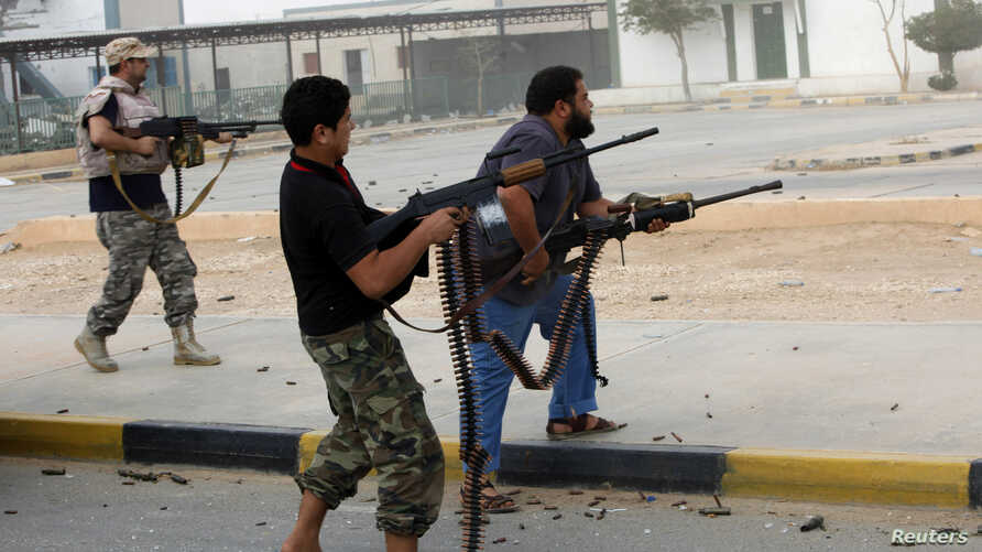 Militia fighters are seen shooting at a building in center of Bani Walid, Libya, October 24, 2012.