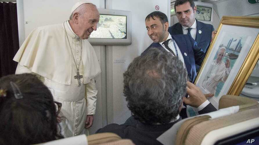 Pope Francis receives a gift from a journalist during his flight from Abu Dhabi to Rome, Feb. 5, 2019.