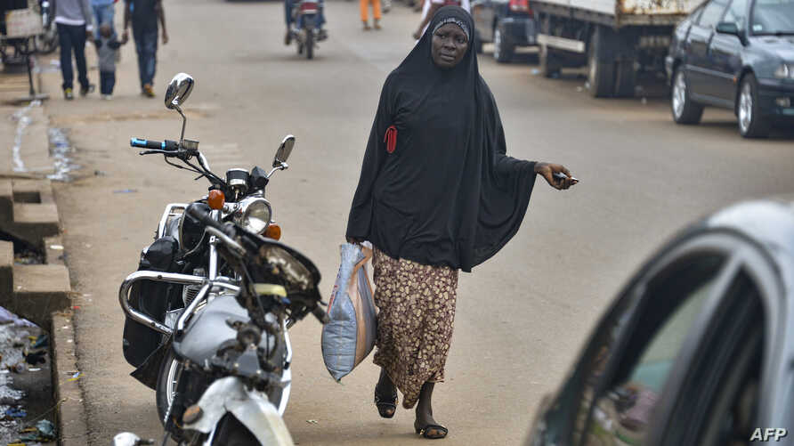 A Muslim woman walks in the Brituetterie district of Yaounde, Cameroon, July 16, 2015.