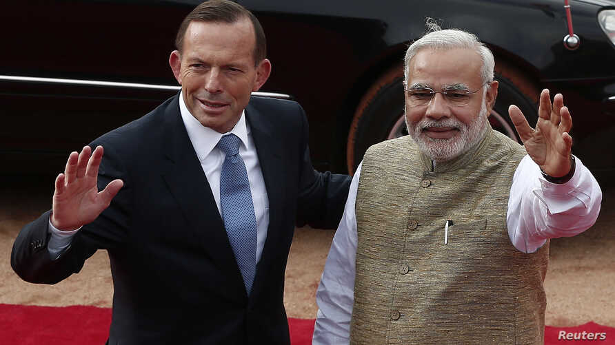 Australia's Prime Minister Tony Abbott and his Indian counterpart Narendra Modi (R) wave towards the media during Abbott's ceremonial reception at the forecourt of India's presidential palace Rashtrapati Bhavan in New Delhi, Sept. 5, 2014.