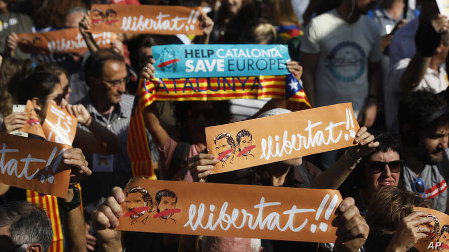 Protesters holds banners that read in Catalan '' freedom'' showing the portraits of the inprisoned Jordi Sanchez and Jordi Cuixart, leaders of the Catalan grassroots organizations Catalan National Assembly and Omnium Cultural, during a rally outside