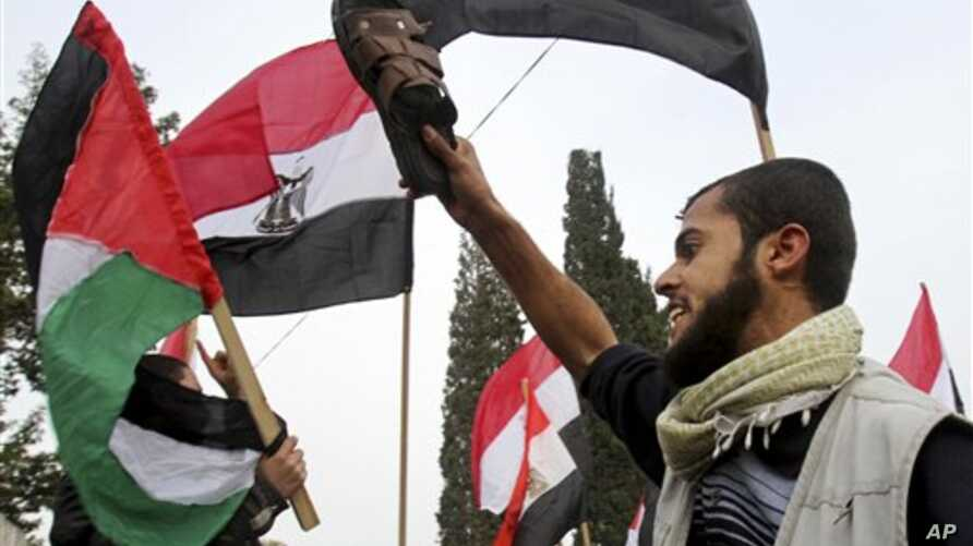 A Palestinian protester holds a shoe as others wave Palestinian and Egyptian flags during a demonstration calling for the removal of Egyptian President Hosni Mubarak in Gaza City, Feb 3, 2011