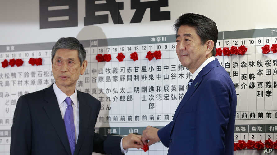 Japanese Prime Minister Shinzo Abe, right, leader of the Liberal Democratic Party, poses with vice president Masahiko Komura for photos as he marks on the name of one of those elected in the parliamentary lower house election at the party headquarter...